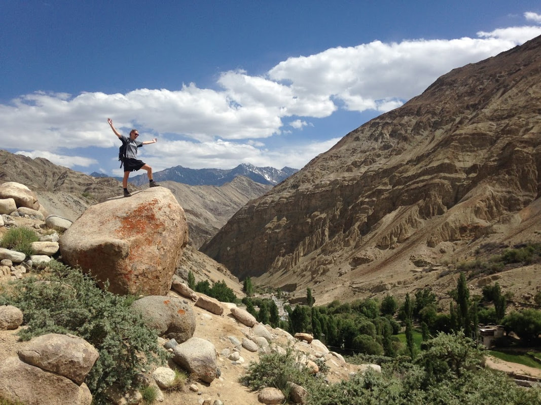 Person on top of a rock with mountains in the background