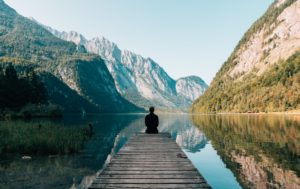 Man sitting on dock looking at mountains