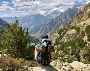 Female hiker with a backpack sitting and looking at mountains