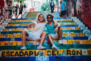 two friends sitting together on colorful steps